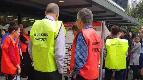 University wardens gather in an assembly area following an evacuation drill.