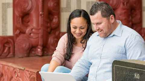 a man and woman looking at laptop in front of a marae
