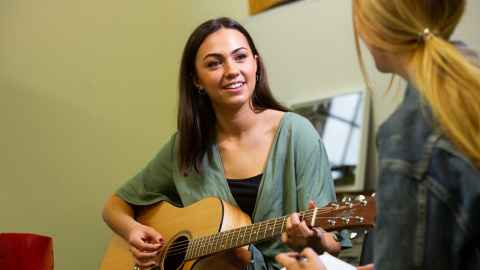 Student playing guitar, looking at another student with notes and pen in her hand