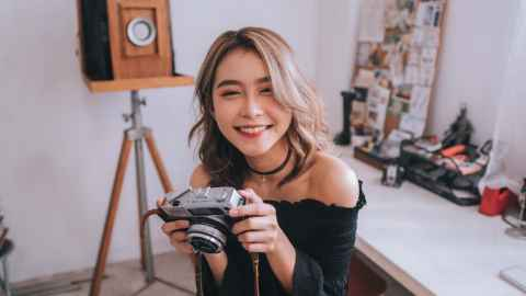 Cheerful student holding a camera