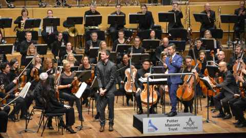 The Auckland Philharmonia Orchestra applaud Josiah Carr after performing one of his pieces