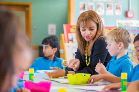 teacher sitting down with children at table