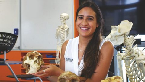 Sina Leilua inside a biology lab holding a model skeleton