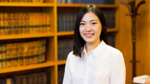 Photograph of Jessie Jiang standing in front of shelves of Law books.