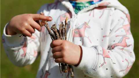 child holding sticks