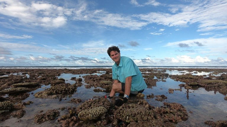 Dr Eddie Beetham is looking at a reef-fringed coral coastline.