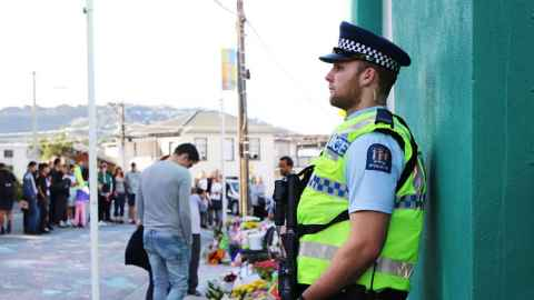 A heavily armed police officer guards the Kilbirnie Mosque the day after the Christchurch terrorist attack. Photo: Lynn Grieveson