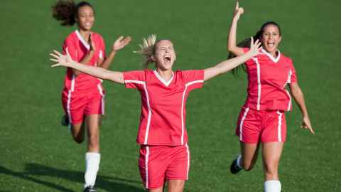 Exuberant female footballers are pictured celebrating goal success: but such celebrations by a victorious US FIFA World Cup team brought criticism that Professor Toni Bruce believes would never be applied to male teams. Photo: iStock