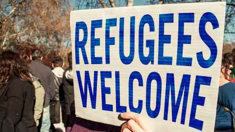 "A participant in a street gathering holds up a sign saying ""Refugees Welcome"". Photo iStock"
