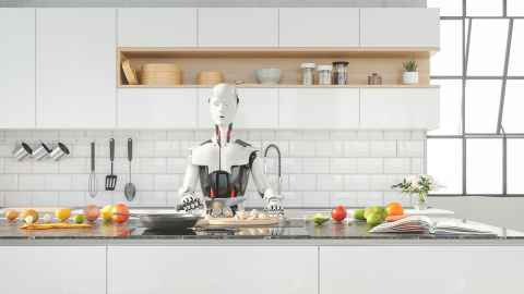 A robot is pictued preparing food at the counter of a smart contemporary kitchen: Robots taking over our domestic chores? Alas, they've barely made it through our front doors says Craig Sutherland.