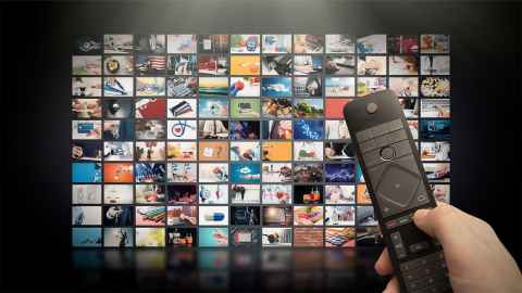 A large TV screen displays multiple video streaming site and a remote in the hand of an unseen user is in the foreground: Downstream traffic on the internet today is dominated by video-streaming. Photo: iStock