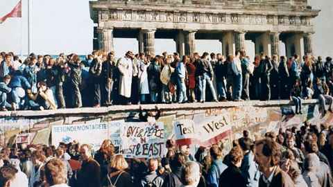 The photo is an iconic image of West and East Germans meeting at the Brandenburg Gate as the Berlin Wall fell in November 1989. Photo: Wikipedia Commons.