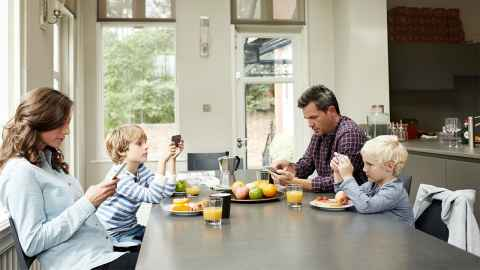 A family sit around a kitchen table, each totally absorbed in their mobile phones: A 'healthy' amount of social media use for adults isn't necessarily 'healthy' for their kids. Photo: iStock kupicoo