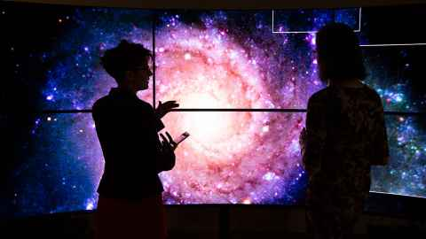 Dr Héloïse Stevance (left) and Dr JJ Eldridge in the Centre for eResearch Visualisation Suite in front of representations of an image of a galaxy.