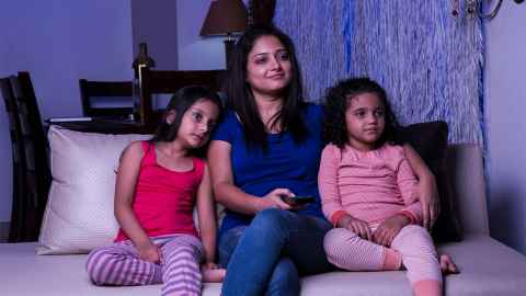 A mother sits with her daughters watching TV: Migrants told researchers their view of Māori changed positively having watched Māori TV. Photo: iStock sit together to watch TV