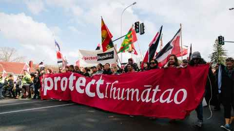 "Protestors blocking the road with a banner declaring ""Protect Ihumātao"" are pictured in an image from last year when the site was capturing headlines. But work has continued behind the scenes explains Dr Hancock. Photo: Emily Parr (Accompany Collective)from last year when Ihumātao was capturing headlines, but work has continued behind the scenes explains Dr Hancock. Photo: Emily Parr (Accompany Collective)"