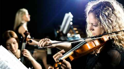 A young female violinist is pictured at the forefront of an orchestra: The decision to downgrade RNZ Concert raises the question of how important it is to support the arts in NZ. Photo: iStock