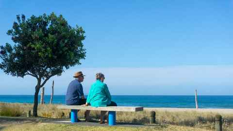An elderly couple in New Zealand are pictured seated on a bench looking out over the ocean. Last year, NZ Superannuation cost the country $14.5 billion. By 2024 it is projected to cost nearly $20 billion a year. Photo: iStock