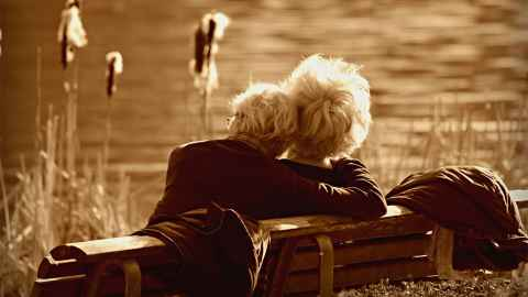 A comfortable-looking older couple relax by a lake: A lot of young people's money is going towards pensioners who don't need it. Stock photo: Pixabay