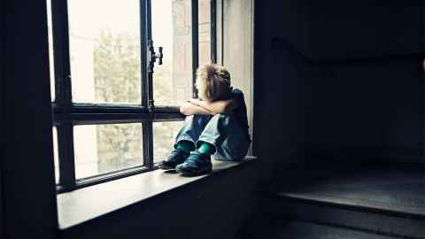 "A small child sits alone on a window sill, his head down on his arms: ""...a different system is required if we really want to make a difference to the well-being of children,"" says Ian Hyslop. Photo: iStock"
