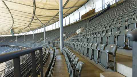 An image shows empty seating across a large stadium. Photo: Achim Scholtya, Pixabay