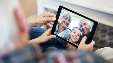 Image of several generations communicating via an iPad