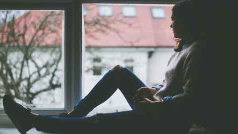 A young woman is pictured sitting on a window sill looking out: Social distancing is hard for people who already feel isolated. Photo: Pixabay