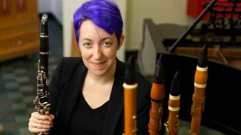 Dr Marie Ross, with a modern clarinet and some of her old ones.