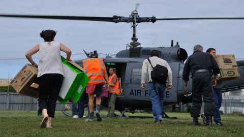 Volunteers are pictured rushing to a helicopter to unload supplies: Voluntary organisation and their armies of volunteers were essential to the rescue operation following the Christchurch earthquakes. Photo: iStock