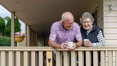 The image shows an older couple on the deck of a house: Friends living together are worse off than friends together in a relationship, but this must change. Photo: iStock
