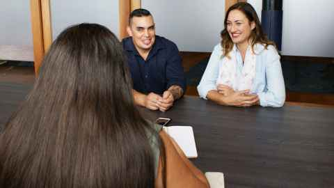 A trio of young New Zealanders sit at a business meeting: Young New Zealanders at the start of their careers must have employment opportunities and not pay the price of Covid-19 alone. Photo: iStock