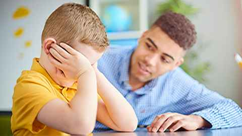 A male teacher is pictured talking to an unhappy young boy with his head in his hands: Caring for a child's well-being and safety is an integral part of teaching but little training is provided in precisely what this involves. Photo: iStock