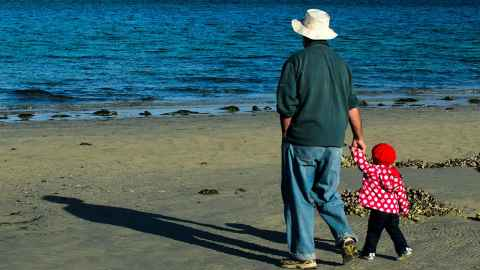 The image shows a grandad with a small grandchild hand-in-hand on the beach: The financial pain post-Covid must be fairly shared across the generations. Photo: iStock