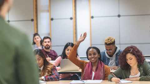 A small class of students looking animated and happy is pictured with the soft focus form of a lecturer on the side of the photo: Without real bodies in a physical classroom, education loses its beating heart. Photo: iStock