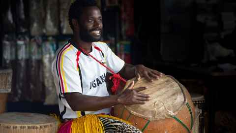 Alfdaniels Mabingo in Ugandan shirt and with drums.