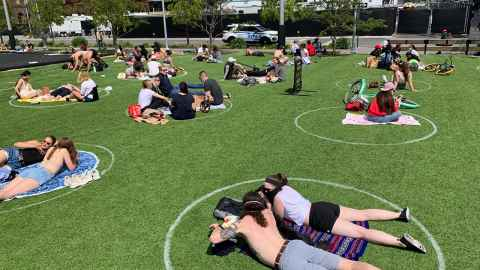 The image shows Domino park in Williamsburg, New York, where people are sitting in large white circles marked on the grass to accommodate social distancing. Photo: iStock