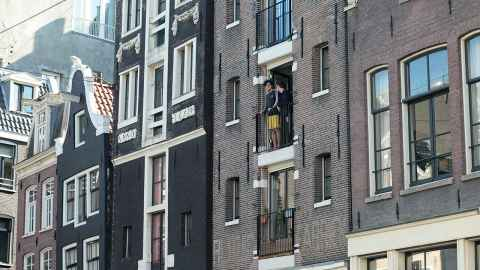 People in quarantine get their fresh air from balconies in Amsterdam.