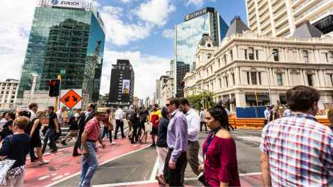 An image shows a crowd of people crossing a busy Auckland street: We need to arrange our cities so the healthy choice is the easy choice, so people can naturally and easily keep their distance, explain Alistair Woodward and Kirsty Wild. Photo: iStock