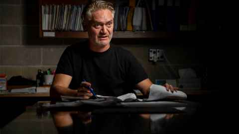 Anthony Hoete, Professor of Architecture, sitting at his drawing board.