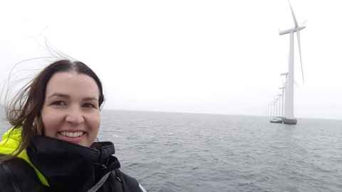 The image shows Dr Julie MacArthur at Denmark's Middlegrunden offshore windfarm, co-owned by a  Copenhagen city-owned utility and the Middlegrunden Co-operative. Photo: Julie MacAthur