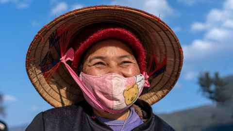 The image shows an older woman wearing a facemask in Sapa, North Vietnam. Photo: iStock