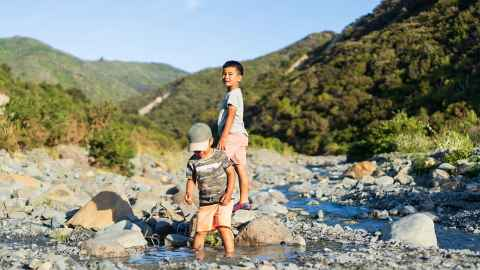 Two young boys are pictured playing in a rocky stream in a New Zealand landscape: Play could be the key to unlocking our children's emotional well-being during these strange times. Photo: iStock