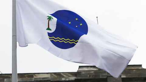 The image shows a flag with the Pacific Island Forum logo fluttering in a breeze. The logo features a deep blue circle with two yellow wavy lines at the bottom and fours yellow stars at the top. There is a cut out of the circle on the left with a palm tree inside. The logo is on a white background.