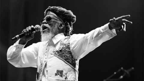 The image shows a recent image of Bunny Wailer singing on stage: Bunny walked this world as a proud Rastafarian and, despite some digressions into disco and dancehall, he remained identified with roots reggae and his Rastafarian beliefs. Photo: Peter Verwimp, CC0, via Wikimedia Commons