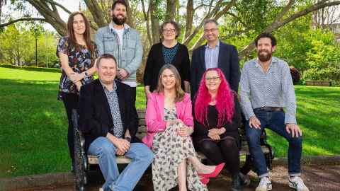 The image shows The modelling team when they were finally able to meet in person - they are sitting on and around a park bench. They are: Dr Emily Harvey, back left, Dr Oliver Maclaren, Associate Professor Ilze Ziedins, Andrew Sporle. From front left, Professor Shaun Hendy, Kate Hannah, Associate Professor Siouxsie Wiles, Dr Dion O'Neale. Photo: Billy Wong