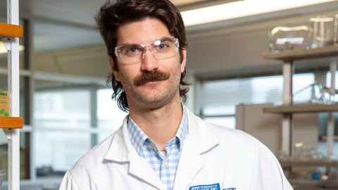 Dr Joel Rindelaub from the Faculty of Science in which white coat and glasses sporting a moustache and mullet.