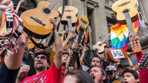 The photos shows protesors with guitars aloft: Thousands sang Victor Jara's 'El derecho de vivir en paz' (The right to live in peace) when more than one million people took part in a street protest in Santiago in 2019. Photo: Wikicommons