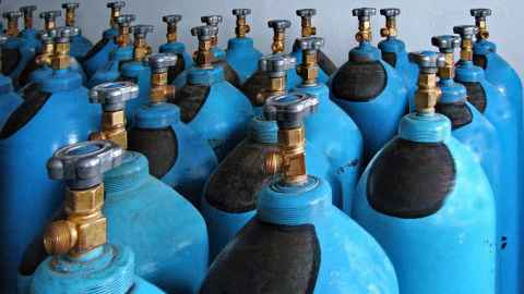 The image shows rowns of medical oxygen tanks: Storing oxygen can be expensive and dangerous if you don't have good systems. Photo: iStock
