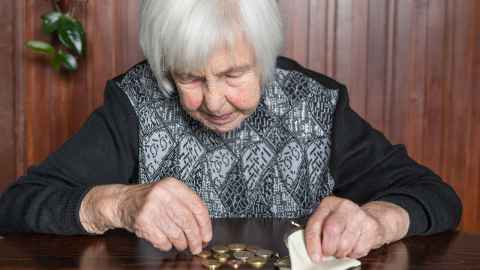 The image shows an elderly woman counting up coins from her purse: Lower earnings-related pension income and longer life expectancy are among the main drivers of higher poverty incidence among women than among men.  Photo: iStock