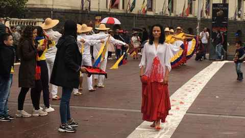 The image shows performance artist and article co-author Alejandra Jaramillo Aristizabal in the foreground wearing a white shirt coated in red paint to represent blood and fellow Colombians dancing in national dress in the background: Bringing the voice of Colombians to Aotea Square on Sunday and showing support for the people making anti-government protests in their home country. Photo: Supplied